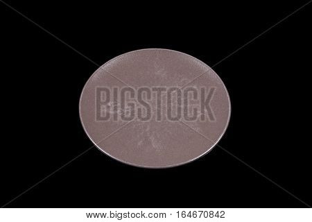 Dark brown flat shallow ceramic plate on black background directly from high angle
