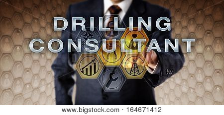 Male recruitment executive in blue business suit is activating DRILLING CONSULTANT on an interactive virtual computer screen. Oil and gas industry job concept for leadership in exploratory drilling.