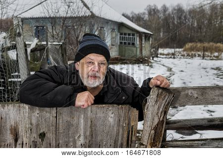 Outdoor portrait of lonely Ukrainian old man with tearful face standing at his fence near neglected house in rural Ukrainian village