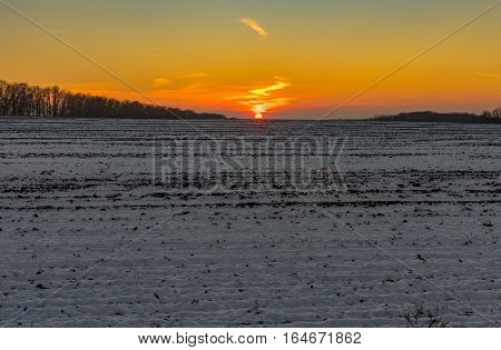 Sunset over agricultural field at winter season in Ukraine