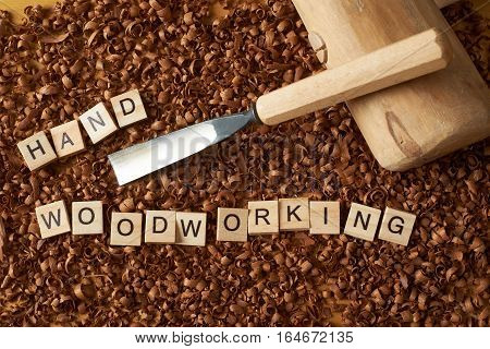 Hand woodworking word writen with letters on wood chips with chisel and a mallet