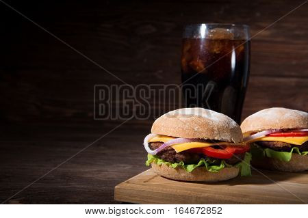Two Bbq Hamburgers With Cola On Wooden Background.