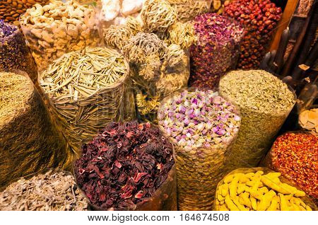 Amazing traditional souk market in Dubai creek district Deira with different baskets full of spices Dubai United Arab Emirates.