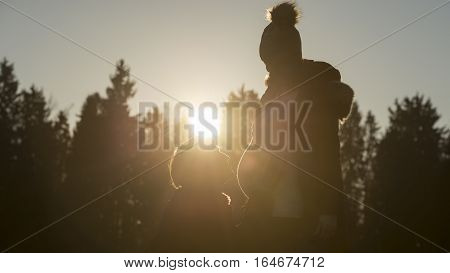 Silhouetted man kneeling by pregnant partner at sunset with trees in background with sunflare.