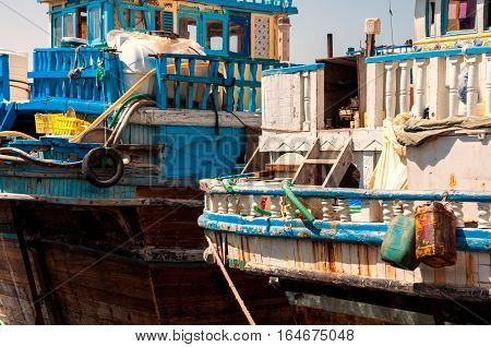 Traditional Wooden Dhows Boats In Dubai Creek District Dock During Busy Trading Day With Sunny Blue