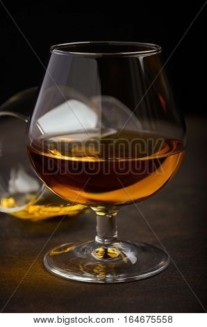 Glass of brandy or cognac on the old rusty background, selective focus, vertical