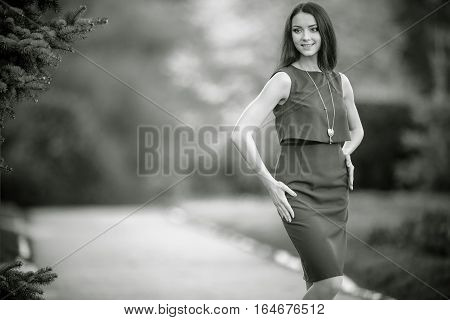 smiling beautiful young woman wearing necklace posing outdoor. Black and white photography