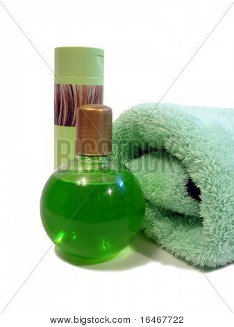 green bottle of shampoo and liquid soap with towel over white