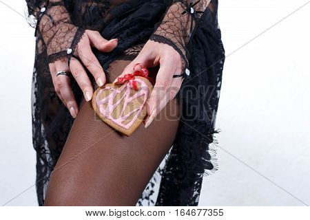 Female hands in black lace gloves hold heart shaped gingerbread cookie with red ribbon against stocking body in black transparent lace dress incognito close up. Valentine's day and love concept