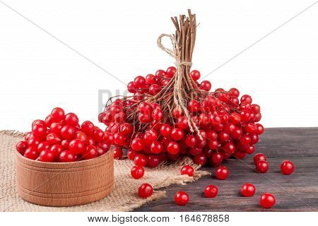 ripe red viburnum berries in a wooden bowl on the table isolated on white background.