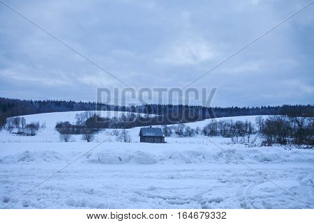Wooden shed stands in the middle snow, snow-covered hills behind and the forest