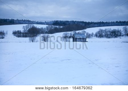 Wooden shed stands in the middle snow, snow-covered hills behind and the forest, close-up