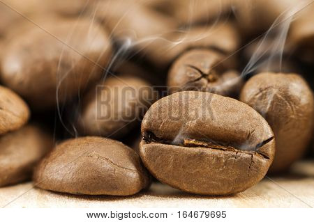 Brown coffee beans with white smoke vapour on yellow textured wooden board background close up.