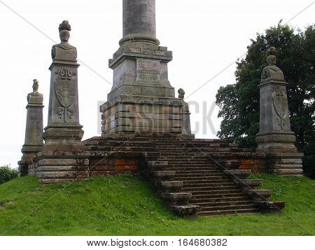 A stone monument dedicated to the Earl of Carlisle on a hill with detailed and decorative pillars and stairs in the countryside in Yorkshire province of England.