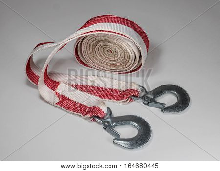 Tow rope to the car on a light background. Rope folded in circle, a coil is on one side, the hooks are there.