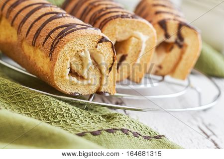 Sweet swiss rolls (roulade) with white cream on green tablecloth
