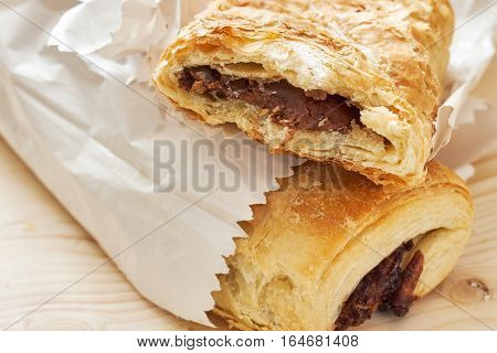 Puff pastry with chocolate filling in white paper bag on wooden background