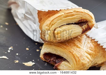 Puff pastry with chocolate filling in white paper bag on black wooden background