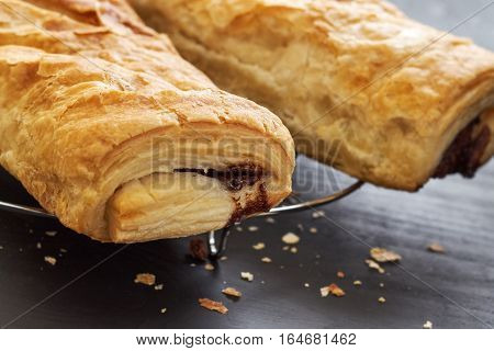 Puff pastry with chocolate filling on black wooden background
