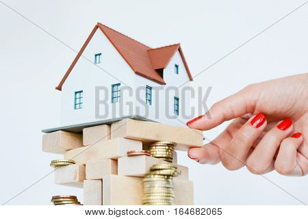 Real estate prices or crisis concept with house on pile of wooden sticks