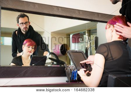woman at the hairdresser's, talking to stylist about her new haircut color. the digital tablet is used to show her a peview of what she will look like.