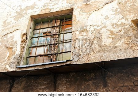 Wall and window with bars. Concrete with cracked paint. The prison of time.