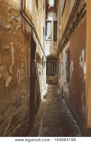 Narrow space between buildings. Aged walls and new windows. Explore the old city district.