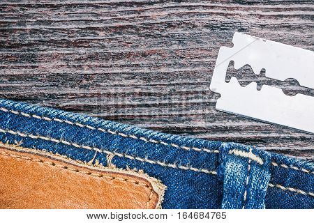 Blue jeans stitched edge and razor blade on dark wood. Macro view