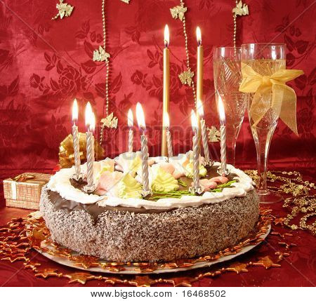 celebratory table (cake and candles, two glasses with champagne, gift boxes) on red