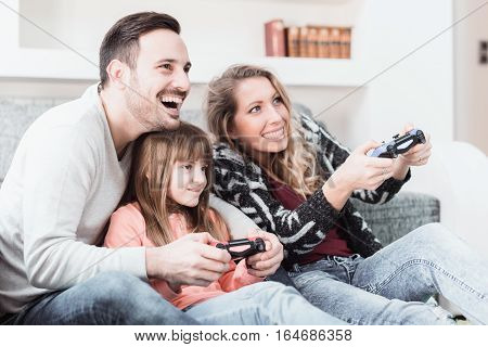 Happy family- father mother and daughter playing a video game at home.