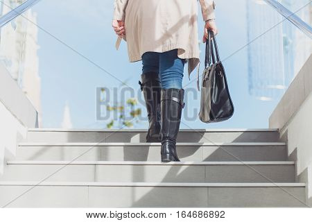 Elegant business woman walking with suitcase outside airport.
