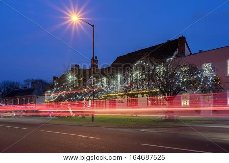 Long Melford, UK. 24th December 2016. Traffic passes through the historic village of Long Melford on Christmas Eve at dusk, captured here as red light trails.