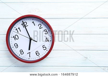 Red Round Clock On A White Wooden Table