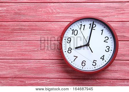 Red Round Clock On A Wooden Table
