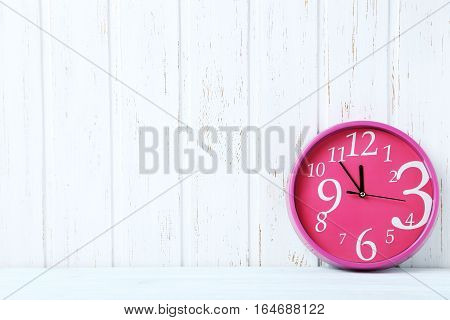 Pink Round Clock On A White Wooden Table