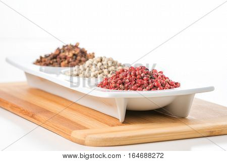 Whole pink peppercorns with white and szechuan peppercorns in the background.