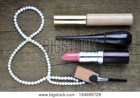 Set of women's cosmetics on wooden backgroung.Lipstick,eyeshadow,mascara,concealer and pearl necklace.Various makeup products on old wooden rustic background.March 8, International Women's Day concept.