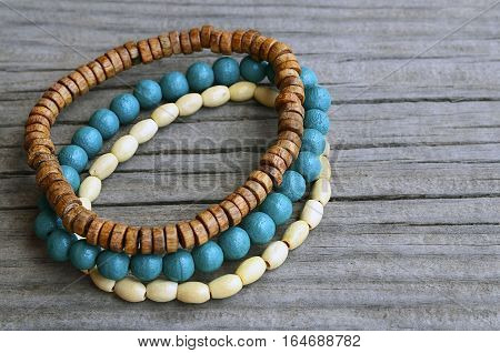 Colorful wooden bracelets on old wooden background.Handcrafted bangles.Handmade wooden bead bracelet.Selective focus.Copy space.