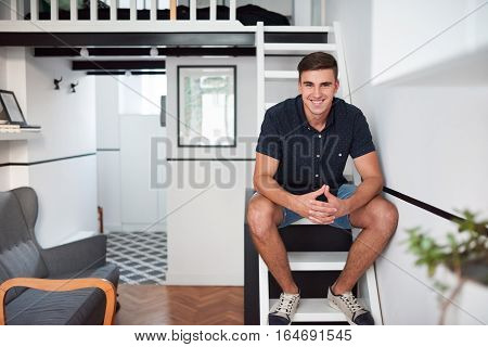 Portrait of a handsome young man smiling while sitting on the stairs in his modern loft apartment