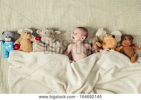 happy baby in a bed covered with a blanket with soft toys