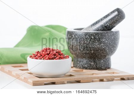 Bowl of whole pink peppercorns with a mortar and pestle in the background.