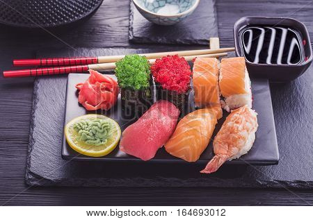Japanese  sushi set and soy sauce on black tableware. Toned