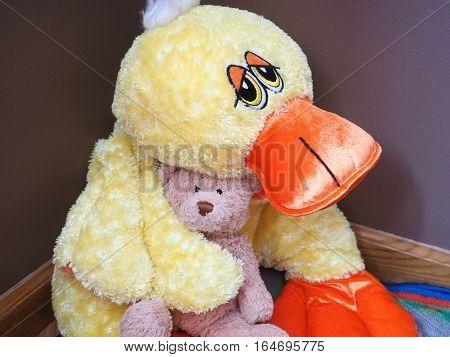Stuffed duck holding a teddy bear on his lap.
