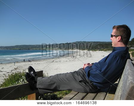 Man Sitting on a Bench Looking at Beach and Ocean