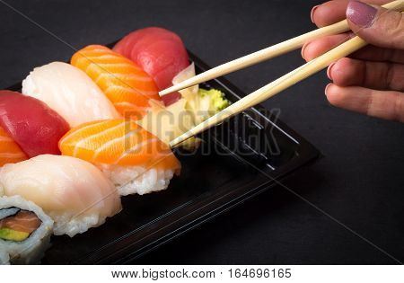 Hand using chopsticks pick Sushi and Sashimi rolls on a black stone slatter. Fresh made Sushi set with salmon prawns wasabi and ginger. Traditional Japanese cuisine.