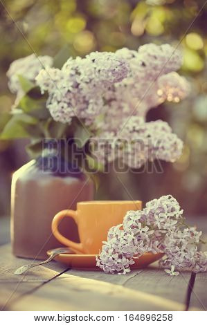 Cup with a spoon and a lilac bouquet in a vase on a wooden table.