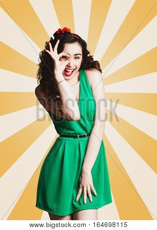 Smiling curly haired Girl brunette in style Pin-up winking and shows gesture OK on yellow rays background.