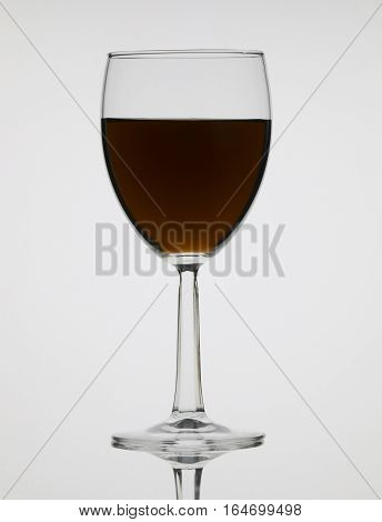 Tall wine glass with liquor isolated on black