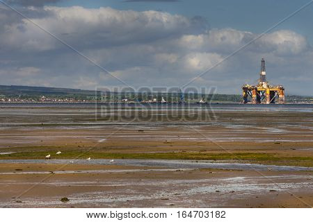 Cromarty Firth Scotland - June 3 2012: Panorama shot of Cromarty Firth at low tide with huge retired and damaged oil drill platform. Wide skies. Green hills. Brown marsh land.