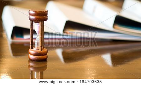 Closeup wooden hourglass waiting the meeting on the table soft and select focus